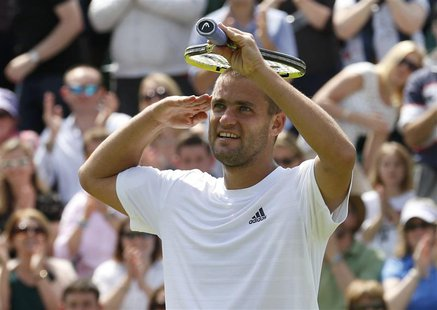 Mikhail Youzhny of Russia celebrates after defeating Viktor Troicki of Serbia in their men's singles tennis match at the Wimbledon Tennis Ch