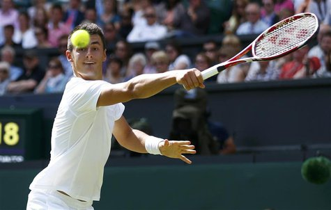 Bernard Tomic of Australia hits a return to Richard Gasquet of France during their men's singles tennis match at the Wimbledon Tennis Champi