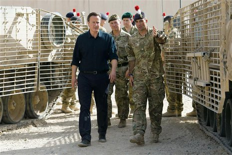 Britain's Prime Minister David Cameron (L) is given a tour of some of the heavy equipment used in operations, during his visit to Camp Basti