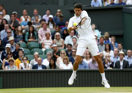 Novak Djokovic of Serbia hits a return to Jeremy Chardy of France in their men's singles tennis match at the Wimbledon Tennis Championships,