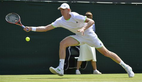 Kevin Anderson of South Africa hits a return to Tomas Berdych of the Czech Republic during their men's singles tennis match at the Wimbledon