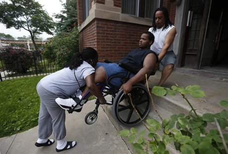 Miles Turner is helped up the stairs to his home by his mother Angela and his father Miles in Chicago, Illinois, June 9, 2013. REUTERS/Jim Y