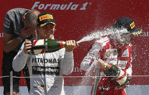 Mercedes Formula One driver Nico Rosberg (L) of Germany celebrates after winning the British Grand Prix with third placed Ferrari driver Fer
