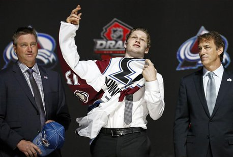 Nathan Mackinnon (C) puts on a Colorado Avalanche jersey after he was selected by the Avalanche as the first overall pick in the 2013 Nation