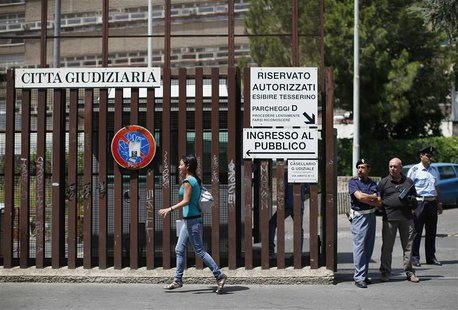 A woman walks past the entrance of the courthouse in Rome June 28, 2013. REUTERS/Tony Gentile