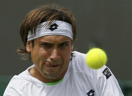 David Ferrer of Spain hits a return to Ivan Dodig of Croatia in their men's singles tennis match at the Wimbledon Tennis Championships, in L