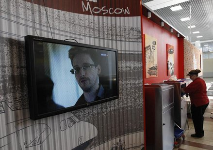 A television screens the image of former U.S. spy agency contractor Edward Snowden during a news bulletin at a cafe at Moscow's Sheremetyevo