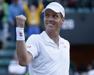 Tomas Berdych of the Czech Republic celebrates after defeating Bernard Tomic of Australia in their men's singles tennis match at the Wimbled