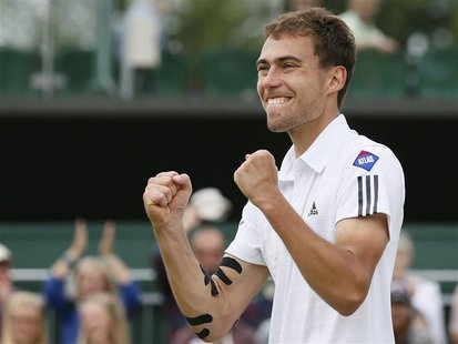 Jerzy Janowicz of Poland celebrates after defeating Jurgen Melzer of Austria in their men's singles tennis match at the Wimbledon Tennis Cha