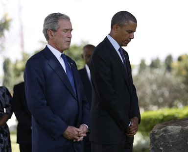 U.S. President Barack Obama and former President George W. Bush (R) attend a memorial for the victims of the 1998 U.S. Embassy bombing in Da