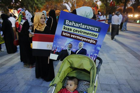 A poster with the pictures of Egypt's President Mohamed Mursi and Turkey's Prime Minister Tayyip Erdogan (R) is attached to a baby stroller