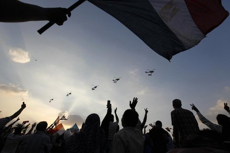 Military helicopters fly above Tahrir Square while protesters opposing Egyptian President Mohamed Mursi shout slogans against him and Brothe