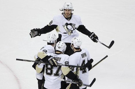 Pittsburgh Penguins Kris Letang (top) skates in to celebrate with teammates Pascal Dupuis, Sidney Crosby and Brooks Orpik (bottom L-R) after