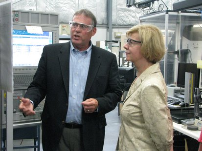 Jim Kinsella, CEO of Pointe Precision, explains a machine's operation to Senator Tammy Baldwin