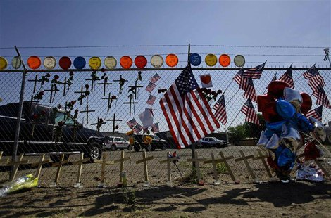 American flags, crosses and balloons are displayed at a makeshift memorial for the 19 firefighters who perished battling a fast-moving wildl