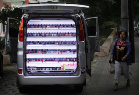 A woman walks past a van which has been converted into a stall selling nail polish on a sidewalk in Beijing, June 4, 2013. REUTERS/Barry Hua