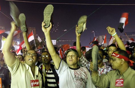 Anti-President Mohamed Mursi protesters hold up their shoes after a speech by Mursi, at Tahrir Square in Cairo July 3, 2013. REUTERS/Mohamed