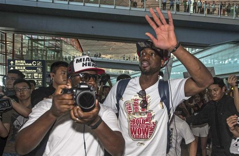 NBA Miami Heat's basketball player Dwyane Wade (front R) waves to fans as he arrives at Beijing Capital International Airport in Beijing, Ju