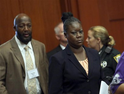 Trayvon Martin's parents Tracy Martin (L), and Sybrina Fulton enter the courtroom after a morning recess in George Zimmerman secondnd-degree