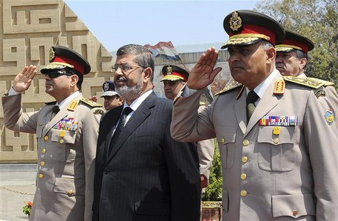 Egypt's President Mohamed Mursi (C) stands after laying a wreath during his visit to the tomb of former President Anwar al-Sadat and the Tom