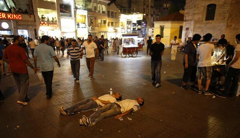 Two protesters lie on the ground of Taksim Square as they stage a silent protest in Istanbul June 29, 2013. REUTERS/Umit Bektas