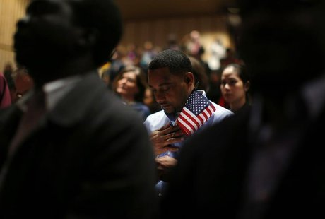 Immigrants stand for the invocation during a naturalization ceremony to become new U.S. citizens at Boston College in Chestnut Hill, Massach