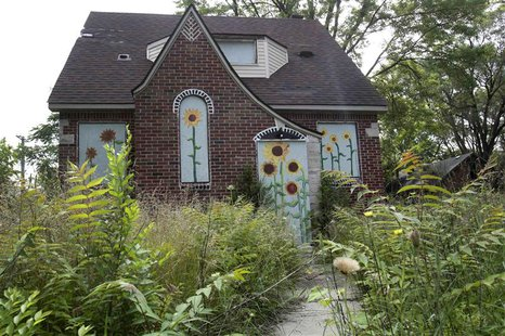 Overgrown grass and weeds are seen around a vacant house that has flowers painted on the boards to keep vandals out in the Brightmoor neighb