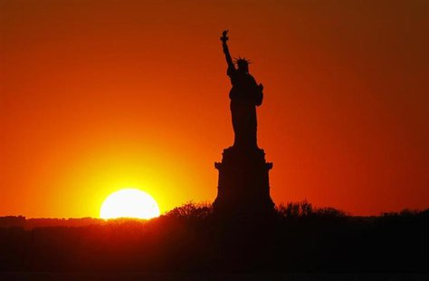 The sun sets behind the Statue of Liberty in New York, May 26, 2013. The statue and Liberty Island will reopen to the public on July 4 after