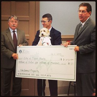 Indiana Attorney General Gregg Zoeller left Buck The Money Dog and his handler center Terre Haute Mayor Duke Bennett  Indiana AG presents unclaimed money check to city of Terre Haute photo provided by Indiana Attorney Generals Office