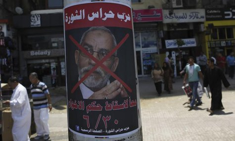 "People walk past a defaced poster of Muslim Brotherhood leader Mohammed Badie with Arabic text which reads ""Together to down brotherhood's p"