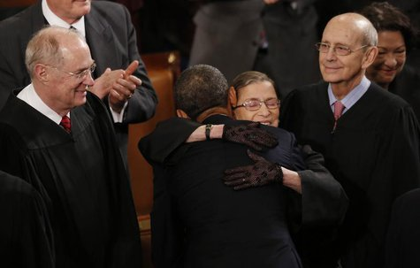 U.S. Supreme Court Justice Ruth Bader Ginsburg hugs President Barack Obama as fellow Supreme Court Justices Anthony Kennedy (L) and Stephen