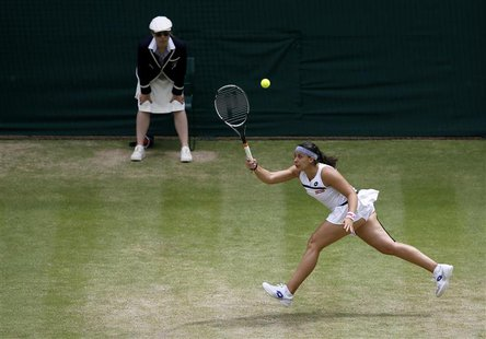 Marion Bartoli of France hits a return to Kirsten Flipkens of Belgium during their women's semi-final tennis match at the Wimbledon Tennis C