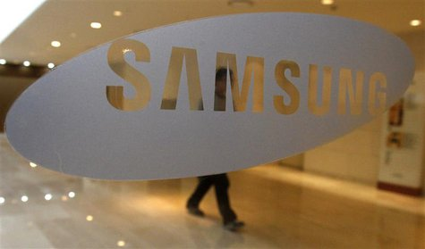 A man walks behind a logo of Samsung Electronics at the company's headquarters in Seoul, in this April 30, 2010 file photo. REUTERS/Jo Yong-