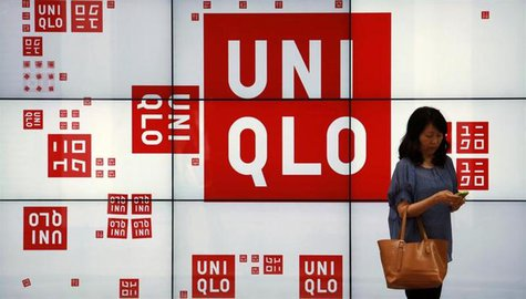 A woman checks her phone in front of a panel outside the flagship store of Japanese fashion house Uniqlo at Hong Kong's Causeway Bay shoppin