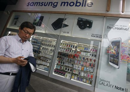 A man uses his mobile phone in front of a Samsung mobile shop in Seoul July 4, 2013. Samsung Electronics Co Ltd estimated its April-June ope