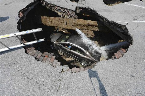Pamela Knox waits for rescue after a massive sinkhole opened up underneath her car in Toledo, Ohio in this July 3, 2013 handout photo provid