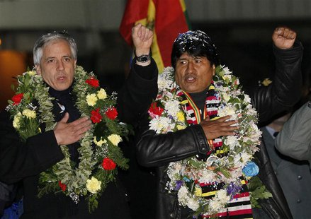 Bolivia's President Evo Morales (R) and Vice President Alvaro Garcia Linera sing the national anthem after Morales' arrival at the El Alto a
