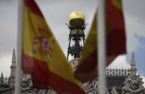 The dome of the Bank of Spain is seen between Spanish flags in central Madrid June 19, 2013. REUTERS/Sergio Perez