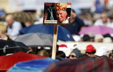 Faithful hold a poster of the late Pope John Paul II as Pope Francis leads a Pentecost vigil mass in Saint Peter's Square at the Vatican May