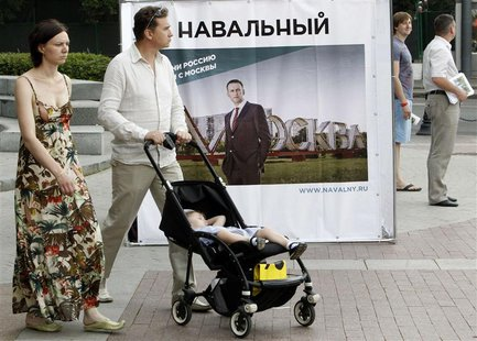 People pass by a banner, part of Russian opposition leader and anti-corruption blogger Alexei Navalny's mayoral election campaign, in Moscow
