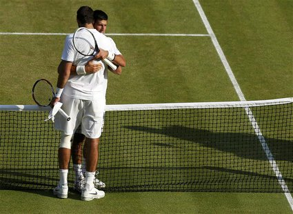 Novak Djokovic of Serbia (REAR) embraces Juan Martin del Potro of Argentina after defeating him in their men's semi-final tennis match at th