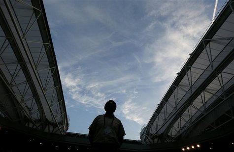 A guard stands on Centre Court as the roof is closed due to fading light during the men's semi-final tennis match between Andy Murray of Bri