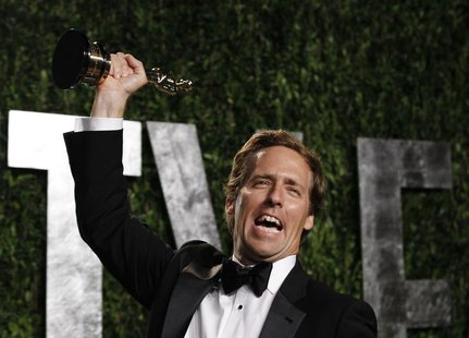 "Nat Faxon holds his award for Best Adapted Screenplay for ""The Descendants"" at the 2012 Vanity Fair Oscar party in West Hollywood, Californi"