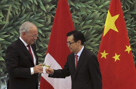 Chinese Commerce Minister Gao Hucheng (R) toasts with Swiss Economy Minister Johann Schneider-Ammann in front of the national flags of Switz