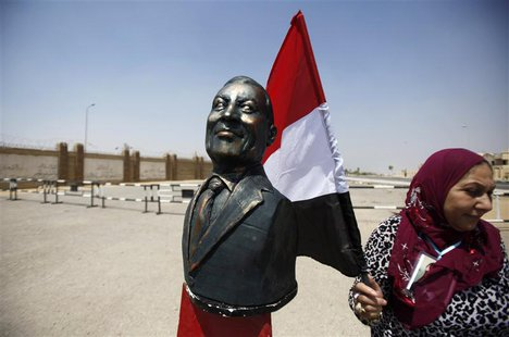 A supporter of Egypt's former President Hosni Mubarak holding an Egyptian flag stands next to a bust of Mubarak outside a police academy whe