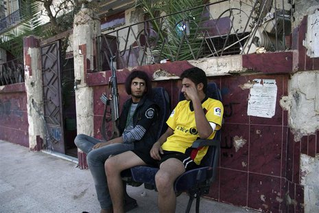 A Free Syrian Army fighter wearing a wig (L), carries his weapon as he sits next to his fellow fighter in Deir al-Zor, July 5, 2013. REUTERS