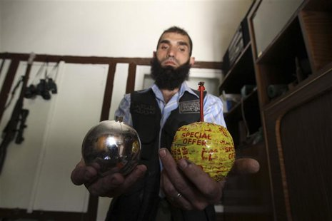 A Free Syrian Army fighter displays homemade bombs made from ornamental balls in the old city of Aleppo July 6, 2013. REUTERS/Muzaffar Salma