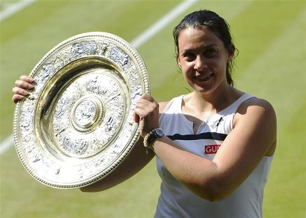 Marion Bartoli of France holds her winners trophy, the Venus Rosewater Dish, after defeating Sabine Lisicki of Germany in their women's sing