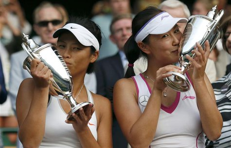 Peng Shuai of China (R) and Hsieh Su-Wei of Taiwan kiss their winners trophies after defeating Ashleigh Barty of Australia and Casey Dellacq