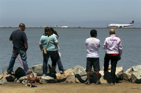 People look from a path along San Francisco Bay after an Asiana Airlines Boeing 777 that crashed while landing at San Francisco Internationa